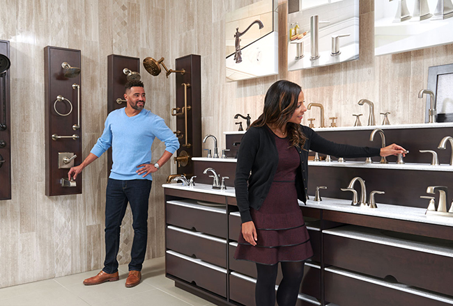 Homebuyers browse a display of bathroom faucets and showerheads at the Home Gallery™