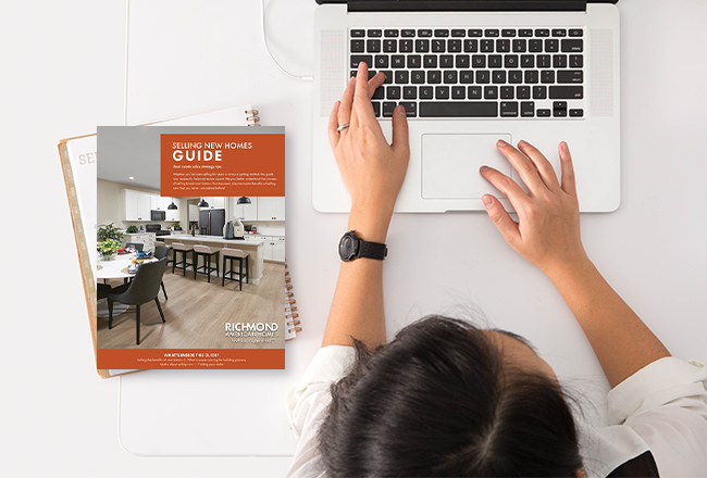 Copy of Selling New Homes Guide next to person typing on computer