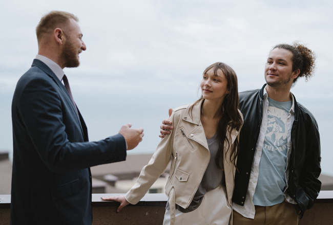 Man in suit talking with couple outside