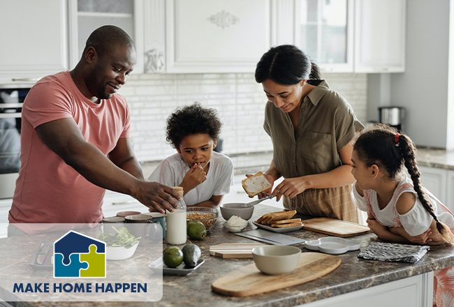 Mom, dad, and two kids around a kitchen island making a meal
