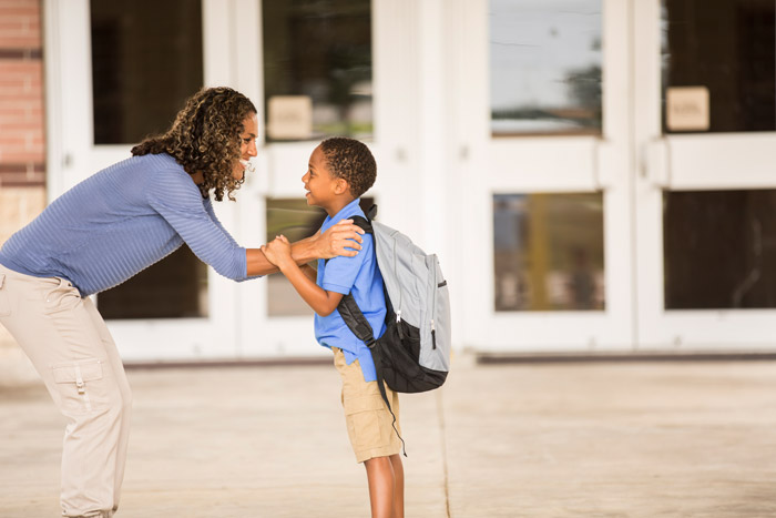 Mother and child with backpack standing in front of school