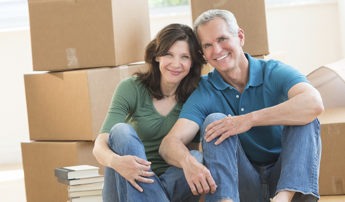 Home in Five: Smiling couple in front of moving boxes