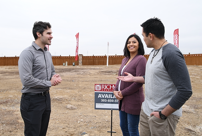 Happy homebuyers standing with their sales associate in front of the homesite they've selected